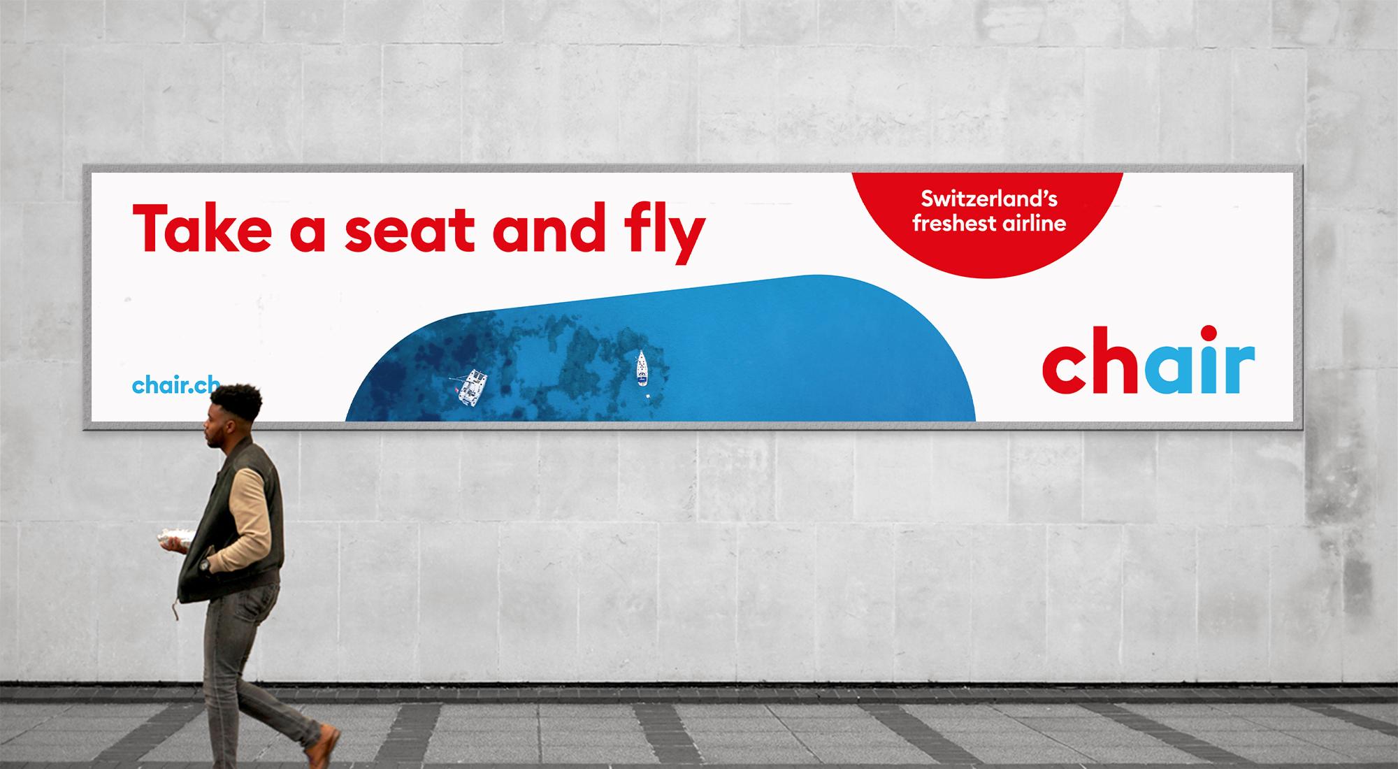 """Langes Billboard an einer Wand mit der Message """"Take a seat and fly"""", einem Meeresbild von oben, dem Claim """"Switzerland's freshest airline"""" und dem chair-Logo."""